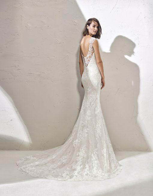 Vestido de novia Fadia de la marca Adriana Alier. De corte sirena, realizado en fino encaje de tul con incrustaciones. Escote joya con tirante ancho y espalda escotada en V.