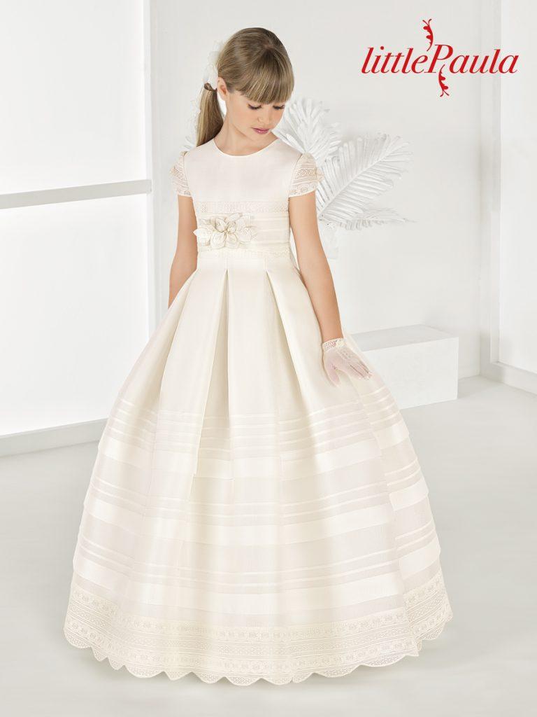 Vestido clásico con falda tableada y lorzas realizado en esterilla marfil con manga corta. Modelo Turia de la colección Little Paula.