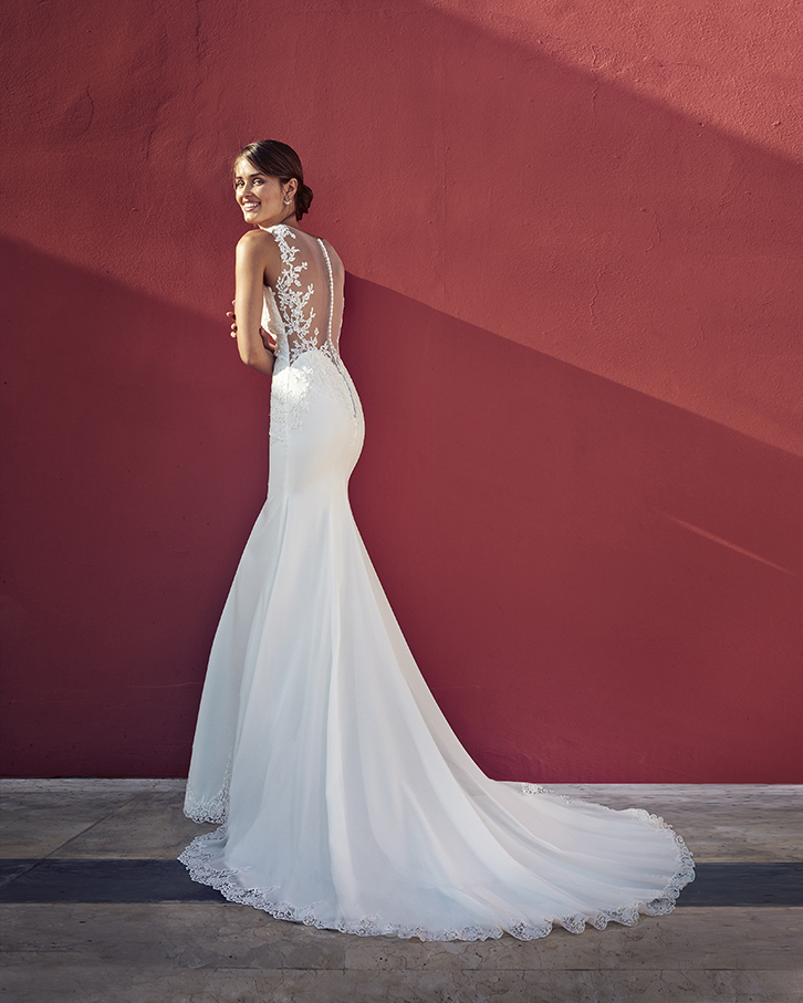 Vestido de novia Fatsia de la marca Adriana Alier. De corte sirena, realizado en fino crepé con incrustaciones. Escote joya con tirante ancho y espalda tatuaje.