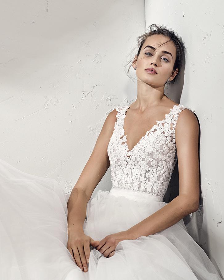 Vestido de novia Frania de la marca Adriana Alier. De corte A, con cuerpo realizado en encaje con incrustaciones y falda lisa de fino tul. Escote en V con tirante ancho y espalda tatuaje.