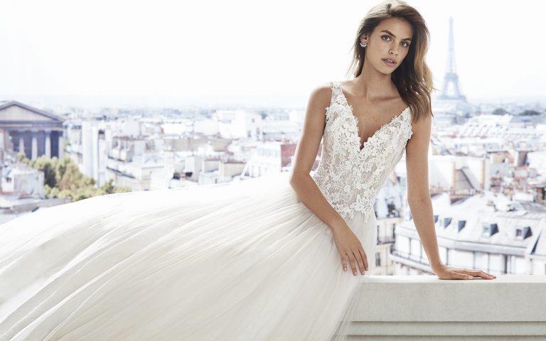 Vestido de novia Vilaflor de la marca Luna Novias. De corte A, realizado en fino tul, con incrustaciones de encaje en cuerpo. Falda lisa con escote en V y espalda descubierta.
